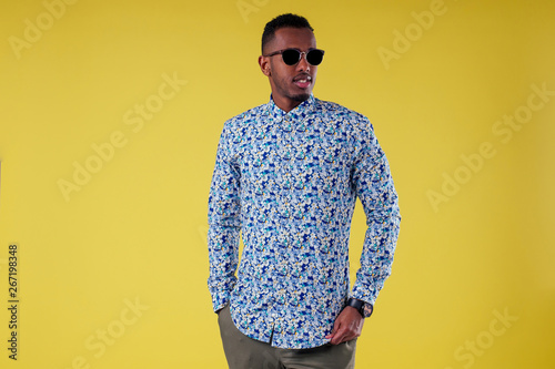 Fotomural  Portrait of attractive young african man sunglasses on yellow wall