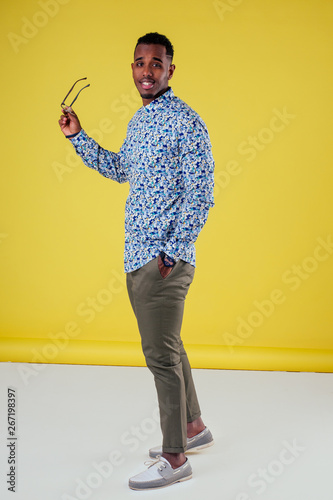 Fotografía  Portrait of attractive young african man sunglasses on yellow wall