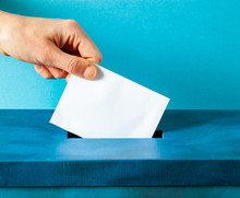 European Union Parliament Election Concept - Hand Putting Ballot In Blue Election Box