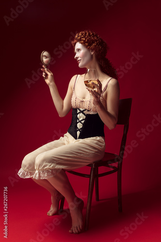 Tableau sur Toile Medieval redhead young woman as a duchess in black corset and night clothes sitting on red background with a mirror and a glass of wine