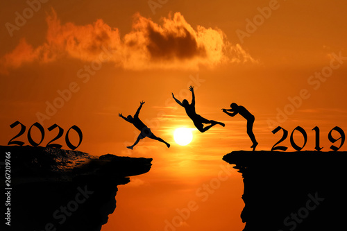 Foto auf AluDibond Ziegel Men are jumped between high cliff at a red sky sunset, Silhouette concept of new year 2020,