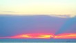 ray of sunset and flame cloud over sea and small island cargo ship on sky line