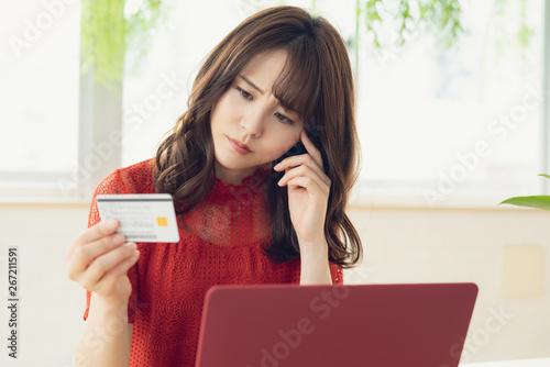Obraz クレジットカードを見る女性 - fototapety do salonu