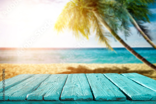 Foto auf Gartenposter Strand Summer background of wooden table and beach background with palms