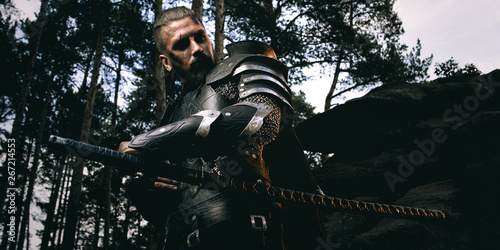 Photo  mystery scarface knight in armor with sword and crossbow in the forest
