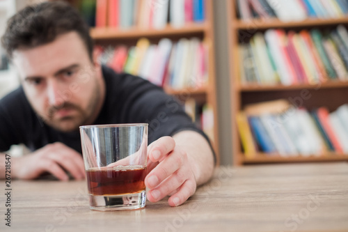 Fotografija  Alcohol addicted man portrait alone with spirit bottle