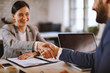 Businesswoman and businessman make a deal and shake hands selective focus on hands
