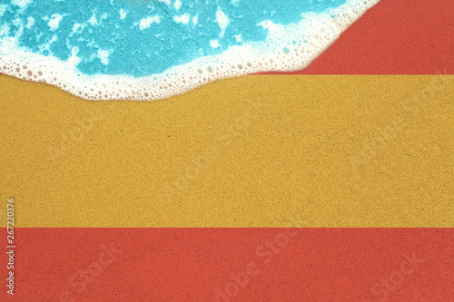 fototapeta na ścianę Sea wave on the sunny sandy beach with flag Spain. View from top on surf.