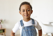 Portrait Of Handsome Cheerful Little Boy Of African Origin Posing Indoors, Having Confident Joyful Facial Expression, Looking At Camera With Happy Smile, Dressed In Denim Jumpsuit Over White T-shirt