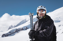 Portrait Athlete Skier In Helmet And Ski Mask Against The Snow-capped Mountains Of A Ski Resort With A Reflection Of The Caucasian Mountains In The Mask