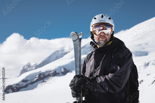 Pinturas sobre lienzo  Portrait athlete skier in helmet and ski mask against the snow-capped mountains