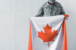 canvas print picture - man in military uniform holding canada national flag while standing near white wall with bowed head