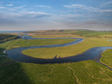 Stunning aerial drone landscape image of meandering river through marshland at sunrise - 267227756