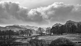 Mody landscape image of Loughrigg Tarn in UK Lake District during dramatic evening in Spring in black and white - 267228355