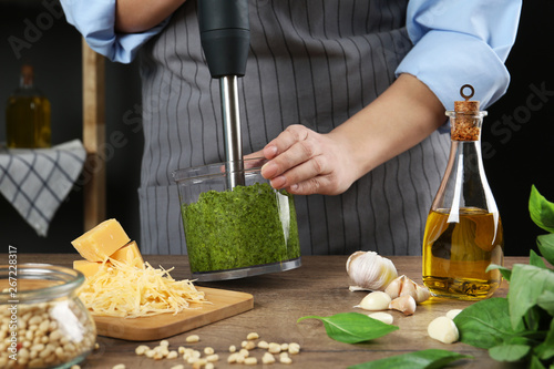 Woman blending pesto sauce in bowl at table, closeup Canvas Print