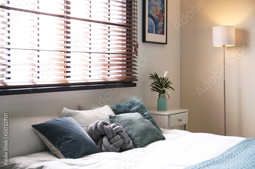 Photo Modern room interior with comfortable double bed and window blinds