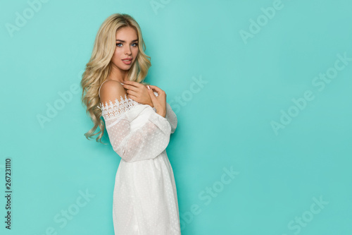 Fotografija  Beautiful Blond Woman In White Lace Dress Is Posing With Arms Crossed At Chest