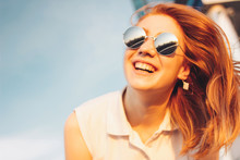 Positive Beautiful Happy Red Haired Girl In The Mirror Sunglasses On Blue Sky Background, Summer Sunset Time