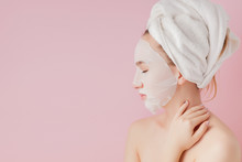 Beautiful Young Woman Is Applying A Cosmetic Tissue Mask On A Face On A Pink Background. Healthcare And Beauty Treatment And Technology Concept