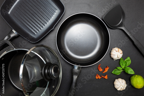 Fotografia Top view frying pan and pot on black leather background