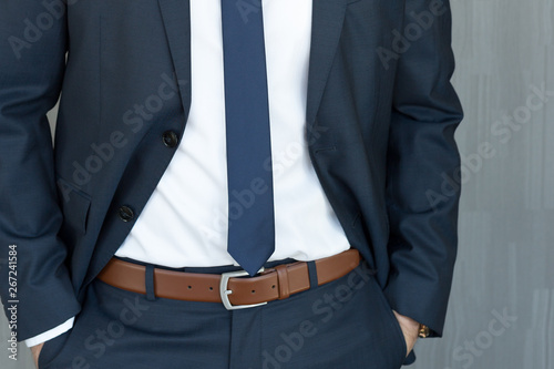 Pinturas sobre lienzo  Torso of anonymous white collar worker standing with hands in pockets, wearing beautiful fashionable classic navy blue suit against grey backgound