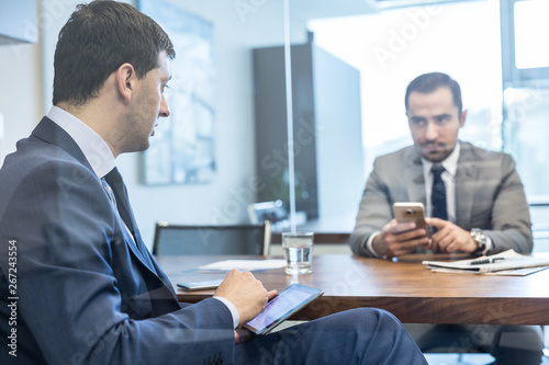 Fototapety, obrazy: Through the window view of two young businessmen using tablet and smart phone devices at working business meeting in corporative office.