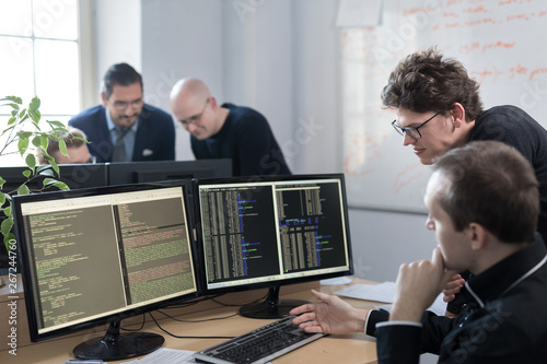 Startup business and entrepreneurship problem solving. Young AI programmers and IT software developers team brainstorming and programming on desktop computer in startup company share office space. - 267244760