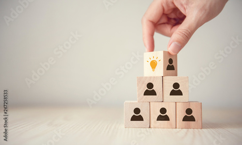 Photo  Leader with idea and innovation, Woman hand flips cube with icon light bulb and human symbol