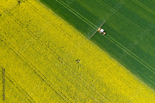 Fototapeta Aerial view of farming tractor plowing and spraying on field.  Agriculture. View from above. Photo captured with drone. obraz