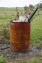 A Rusted Burn Barrel Overflowing With Sticks And Trash.