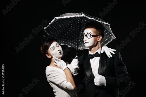 portrait of couple mime with umbrella on black background Canvas Print