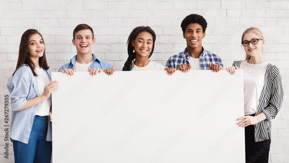 Fototapety, obrazy: Happy teenagers holding empty banner, white brick wall