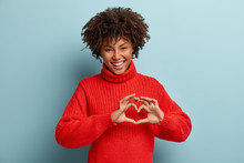 Portrait Of Lovely Female Model Makes Heart Gesture, Says Be My Valentine, Demonstrates Love Sign, Has Glad Expression, Wears Warm Red Jumper, Isolated Against Blue Background. Body Language