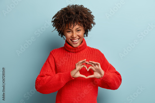 Fototapeta Portrait of lovely female model makes heart gesture, says be my valentine, demonstrates love sign, has glad expression, wears warm red jumper, isolated against blue background. Body language obraz
