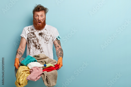 Horizontal shot of stupefied housekeeper carries laundry basket, has dirty cloth фототапет
