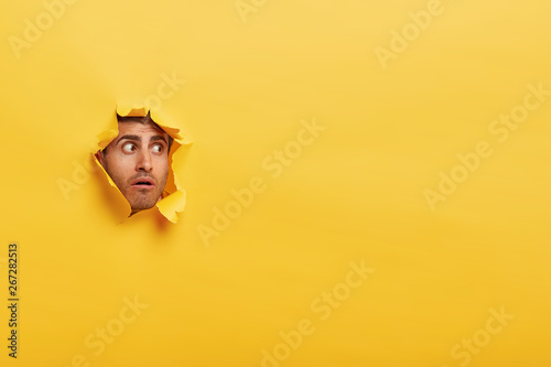 Obraz na plátně  Astonished unshaven man has stupefied expression, peeks through torn wall paper, has widely opened eyes, stares through hole in yellow background