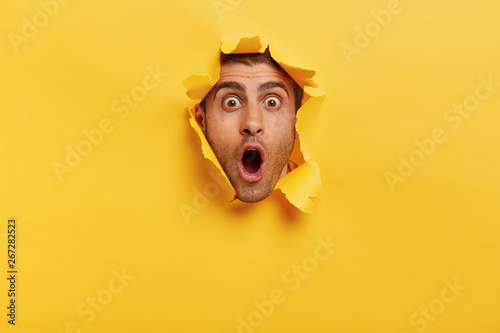 Stupefied young man with bristle keeps jaw dropped from surprisement, has popped eyes, stares through yellow torn paper, impressed by shocking rumors Wallpaper Mural