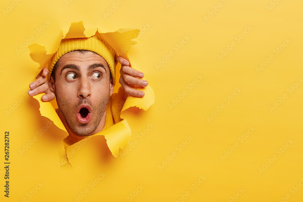 Fototapeta Surprised male face through paper hole. Emotional astonished young man wears yellow headgear, makes slot in background with hands, keeps mouth wide opened. Copy space to insert yout text or slogan