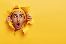 Surprised Male Face Through Paper Hole. Emotional Astonished Young Man Wears Yellow Headgear, Makes Slot In Background With Hands, Keeps Mouth Wide Opened. Copy Space To Insert Yout Text Or Slogan
