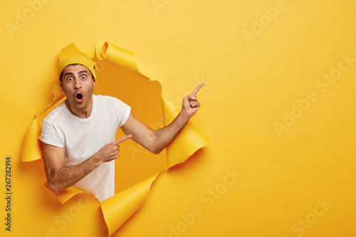 Fotografija  Horizontal shot of surprised young Caucasian man in white t shirt and yellow headgear, has widely opened mouth, indicates at copy space, models in torn paper background