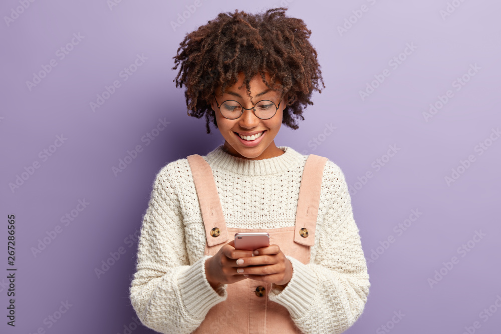 Fototapety, obrazy: Indoor shot of happy curly woman with pleased facial expression, reads nice message from boyfriend, concentrated in smartphone, makes schedule for tommorow, uses new application, smiles at screen