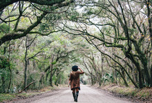 Girl Walking Under Tree Canopy On Dirt Road Through Swamp On Edisto Island In South Carolina