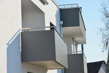 Balkon Mit Metall-Geländer Und Kunststoff-Plattenverkleidung An Moderner Mehrfamilien-Neubau-Hausfront