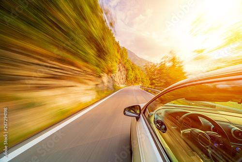 Fotografiet  Car in motion blur driving in the Italian mountains