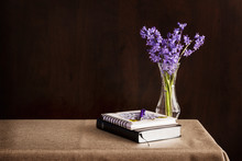 Bible And Journal Placed On A Table With Flowers In Vase; Bible And Journal For Daily Devotions