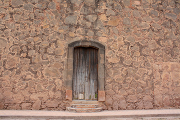 Fototapeta na wymiar Ancient adobe and stone facade in a mexican house