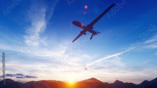 Photo  A military drone flies over a desert mountain plain at sunset