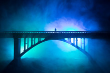 Artwork Decoration. Silhouette Of Powerful Metallic Bridge At Night With Foggy Backlight. Silhouette Of Person Standing On Bridge.