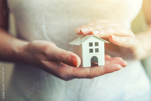 Fotografie, Obraz  Female woman hands holding small miniature white toy house