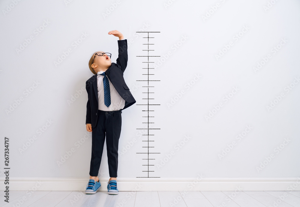Fototapeta Kid is measuring the growth